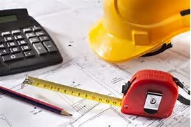 Hard hat and tape measurer over construction plans